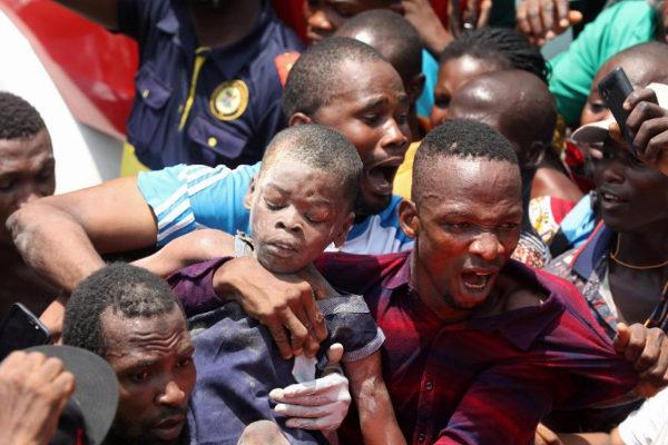 Un hombre sostiene a uno de los niños rescatados en Lagos.