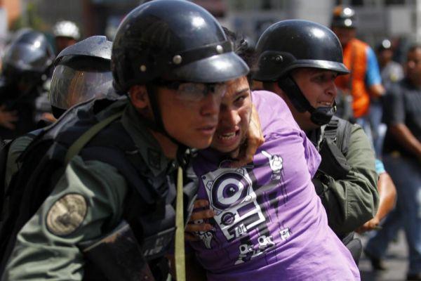La policía del régimen de Maduro detiene a un manifestante en Caracas.