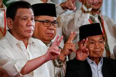 EPA4245. MANILA (FILIPINAS).- Foto de archivo del vicepresidente del Frente Moro de Liberación Islámica (FMLI), Ghazali Jaafar (dcha), mientras posa junto al presidente filipino, Rodrigo <HIT>Duterte</HIT> (izq), durante una ceremonia en el Palacio Malacañang en Manila (Filipinas) el 22 de febrero de 2019. Ghazali Jaafar, vicepresidente del FMLI, el mayor grupo rebelde musulmán de Filipinas, murió en la madrugada de este miércoles a los 75 años a causa de una enfermedad renal.