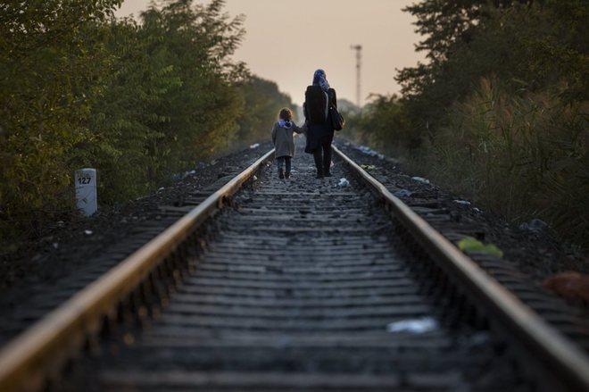 Imagen de una madre y su hija caminando por las vías en Szeged, Hungría.