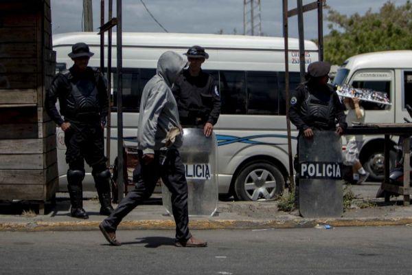 Agentes antidisturbios resguardan una parada de autobús frente a la Universidad Centroamericana, en Managua.