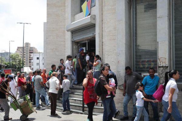 Un grupo de personas hace fila ante un banco.