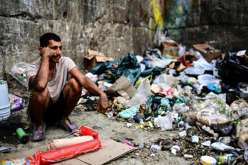 Un hombre espera para poder rebuscar comida en un basurero de un barrio de Caracas.