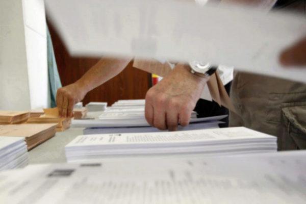 Una mesa electoral con papeletas.