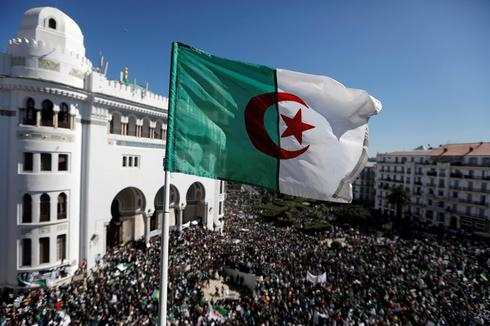 An Algerian flag flutters as people gather during a protest over...