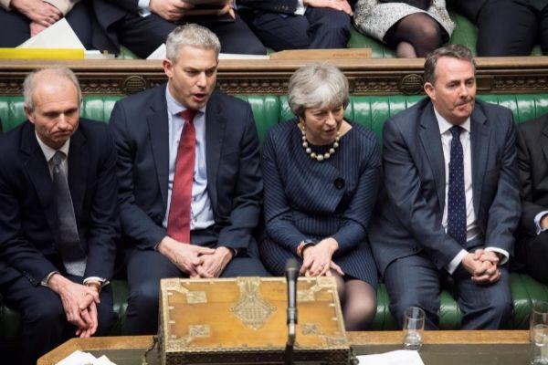 La primera ministra británica, Theresa May (c), junto a miembros de su bancada en la Cámara de los Comunes.