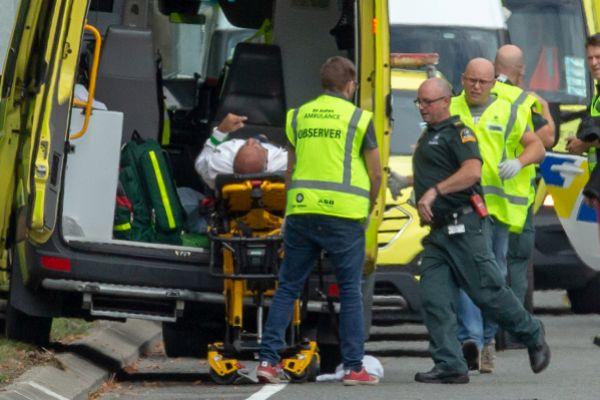 Un herido es trasladado a una ambulancia tras el tiroteo.