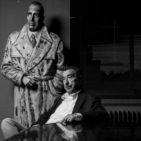 El cineasta José Luis Garci posa delante de una figura de Humphrey Bogart en su productora Nickel Odeon.