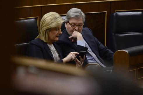 Fátima Báñez e Íñigo Méndez de Vigo, con su móvil, en el Congreso