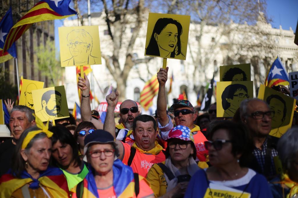 En el centro de Madrid, los manifestantes portan carteles con las caras de líderes independentistas.