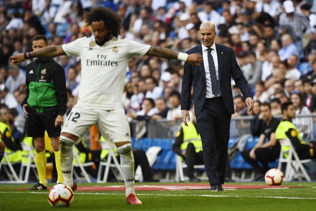 Marcelo controla un balón ante la mirada de Zidane.