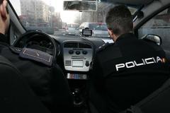 Dos agentes de la Policía Nacional en su coche patrulla.
