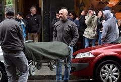 Empleados de la funeraria trasladan el cadáver del joven.