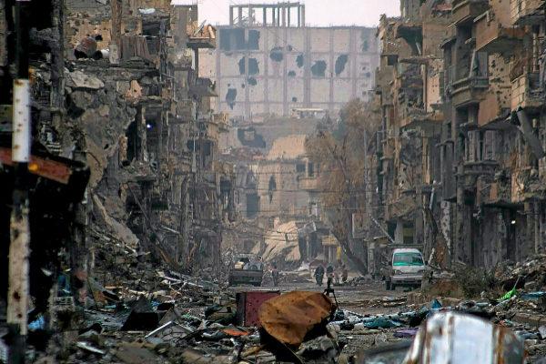 Varias personas caminan entre edificios gravemente dañados por los enfrentamientos en la ciudad de Deir Ezzor (noreste de Siria).