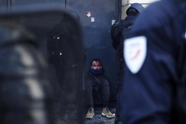 Un herido en las manifestaciones de ayer en París, entre dos antidisturbios.