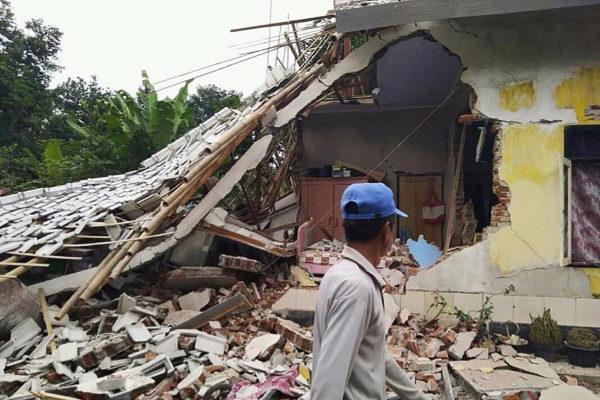 Un hombre observa los efectos del terremoto en una vivienda.