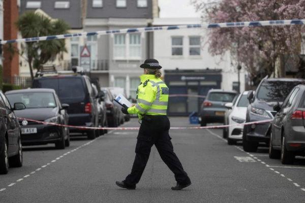 A <HIT>police</HIT> officer walks next to crime scene cordon tape...