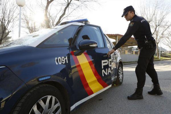 Un agente entrando en un coche de la Policía Nacional.