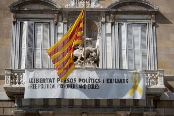 Fachada del Palau de la Generalitat de donde cuelga, junto a la bandera catalana, un cartel y un lazo amarillo.