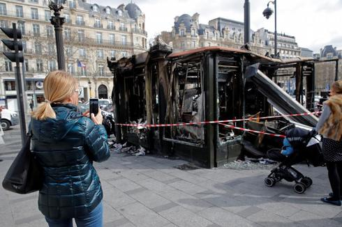 """People take pictures of a newspaper kiosk burned during the last """"yellow vests"""" protest on the Champs Elysees avenue in <HIT>Paris</HIT>"""