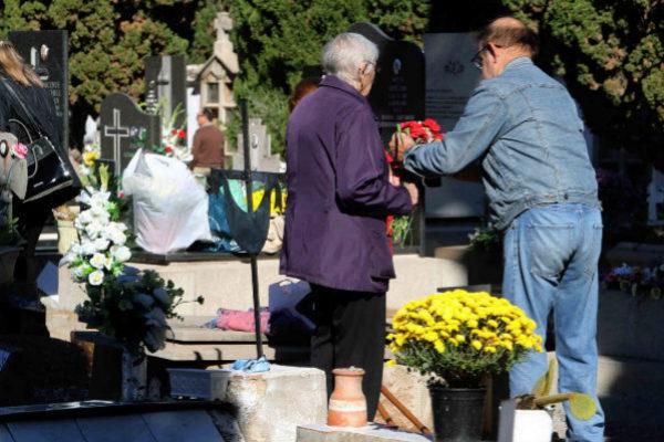 Los familiares arreglan las sepulturas en el día de Todos los Santos.