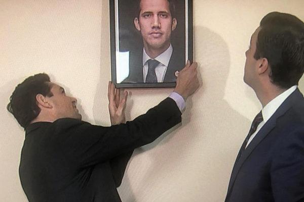 Carlos Vecchio, representante de Guaidó en EEUU, coloca el retrato de éste en la sede de la agregaduría militar de Venezuela en Washington.