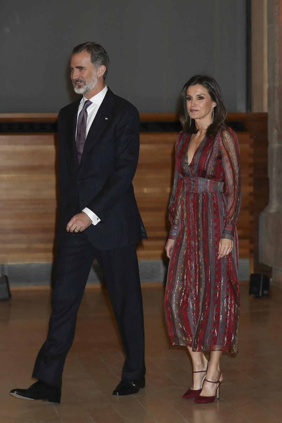 La Reina ha elegido un vestido en tonos granates y con hilos plateados...