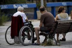 Un anciano conversa con sus familiares, junto a la residencia en la que vive.