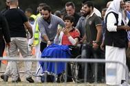 Zaed Mustafa  (C, en silla de ruedas), herido por un pistolero australiano supremacista, asiste al funeral de su padre asesinado, Khaled Mustafa, y de su hermano Hamza Mustafa en el cementerio de Memorial Park en Christchurch.