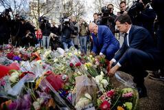 El primer ministro Mark Rutte y el titular de Justicia, Ferdinand Grapperhaus, depositan flores en el lugar del tiroteo.