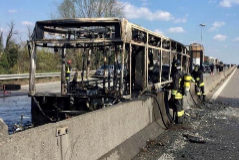 The wrecakge of a burnt out bus is seen on a road in <HIT>Milan</HIT>