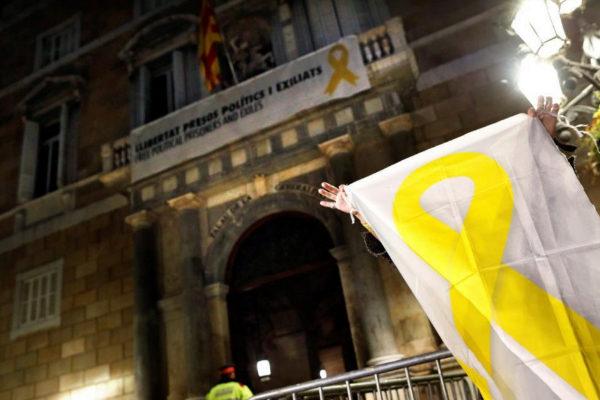 Una mujer muestra una pancarta con un lazo amarillo ante el Palau de...