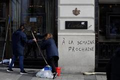 Dos empleadas de limpieza limpian los desperfectos en una tienda de Cartier atacada por los chalecos amarillos.