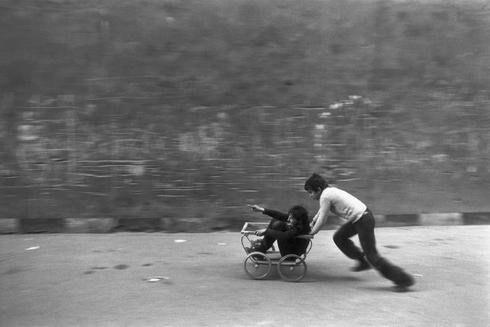 Dos niños jugando en la calle con un carro, en los años 70.
