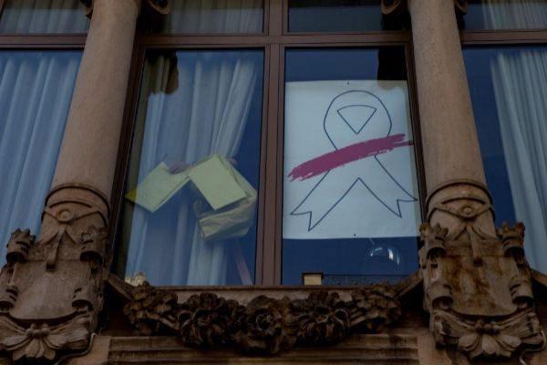 Un operario retira el lazo amarillo de una de las ventanas de la fachada del edificio de la Consejería de Economía.