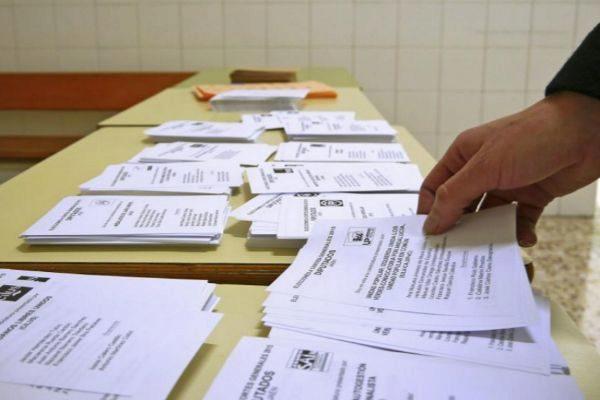 Un votante escoge una papeleta electoral.