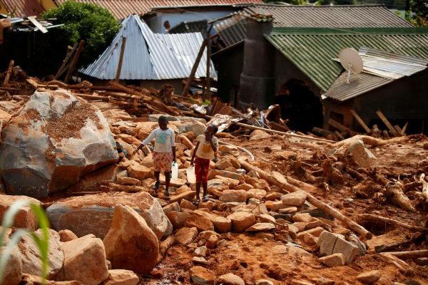 Niños llevando agua potable entre los escombros que ha dejado el ciclón Idai, ayer en Chimanimani (Zimbabue)