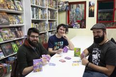 """Domingo Cabrero, Santi Santiesteban y  C. Lopez, creadores del juego de cartas """"Virus"""" posan en la tienda de comics y juegos Generacion X de Rivas-Vaciamadrid."""
