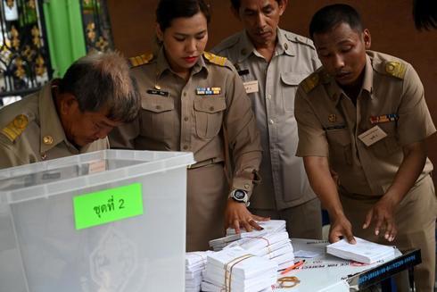 Funcionarios electorales se preparan para contar los votos en una mesa...