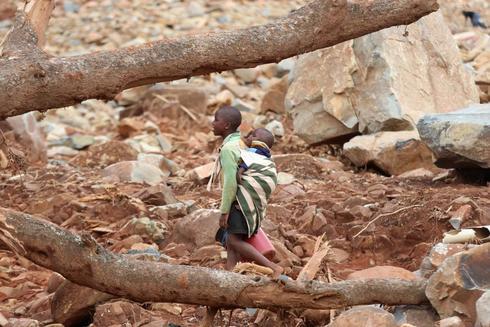Un niño con un bebé en su espalda camina a través de escombros después del ciclón Idai en Ngangu, Chimanimani, Zimbabwe, el 23 de marzo de 2019.