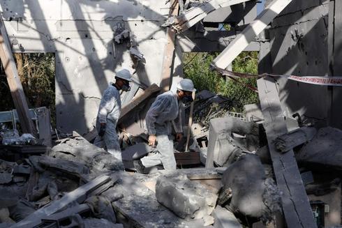 Operarios de rescate inspeccionan la casa alcanzada por el misil.