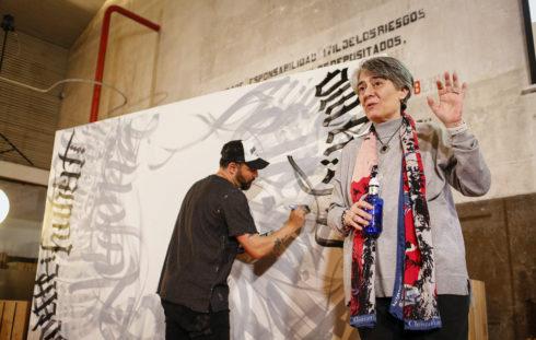 La escritora Matilde Asensi durante la presentación, ayer, de su último libro mientras el artista Mr. Zé realiza un mural