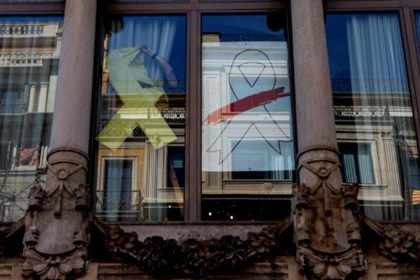 Un operario retira el lazo amarillo de un ventanal de la Consejería de Economía.