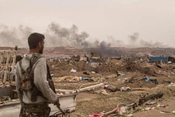 Un combatiente de las SDF observa los escombros de Baguz.