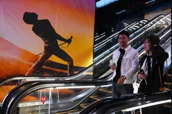 Dos personas pasan frente a un póster de 'Bohemian Rhapsody' en Beijing.
