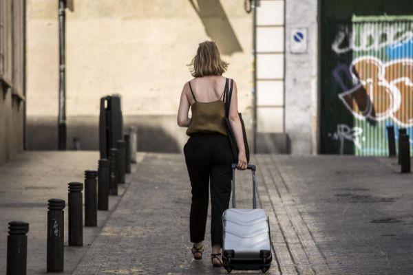Una turista camina con su maleta por el centro de Madrid.