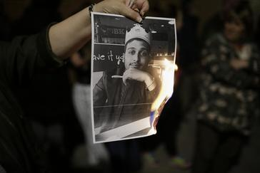Un manifestante sujeta una imagen del sospechoso.