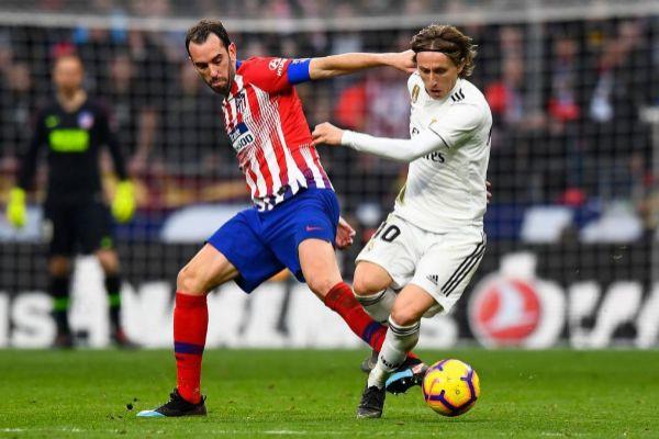 Godín y Modric pelean por un balón en el derbi.