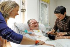 Una médico de la asistencia sanitaria de primaria atiende a un enfermo en su domicilio.