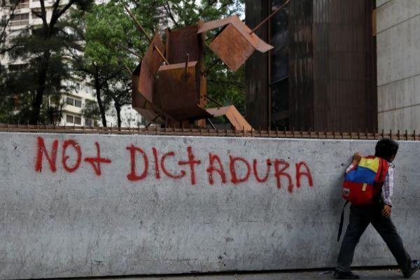 Un niño con una mochila con los colores de Venezuela pasa junto una pintada.